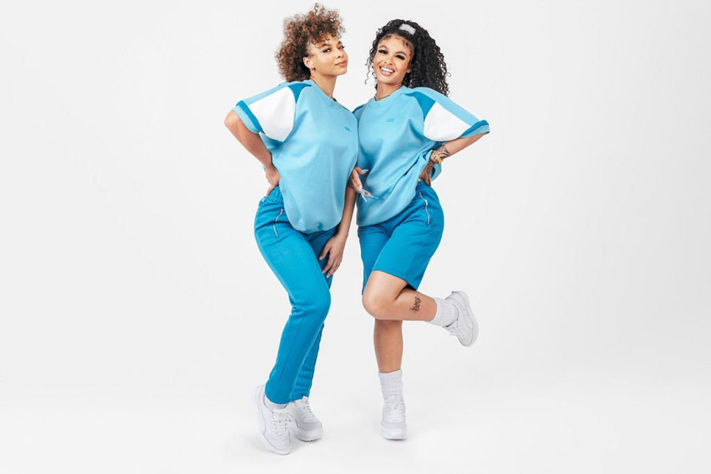 Two women pose in blue tracksuits