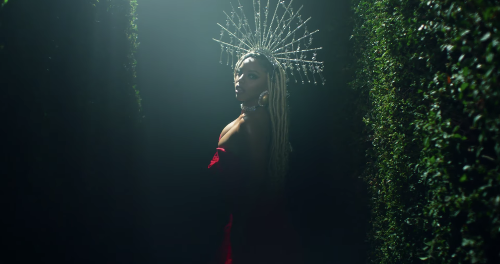 Chlöe wearing strapless red dress and diamond encrusted headpiece surrounded dimly lit greenery